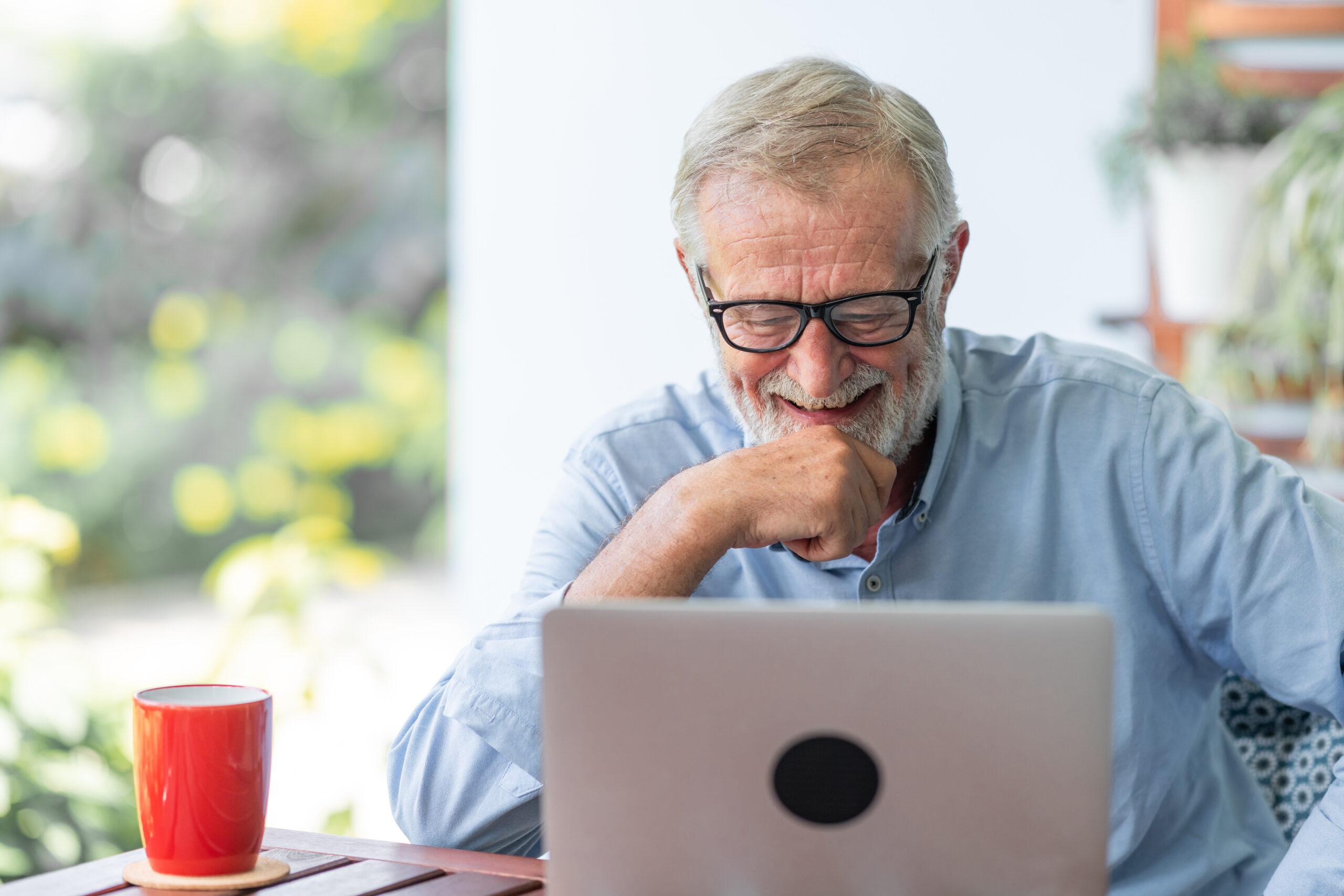 Eldre mann arbeider på PC