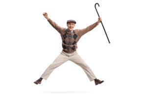 Hoppende glad senior med stokk