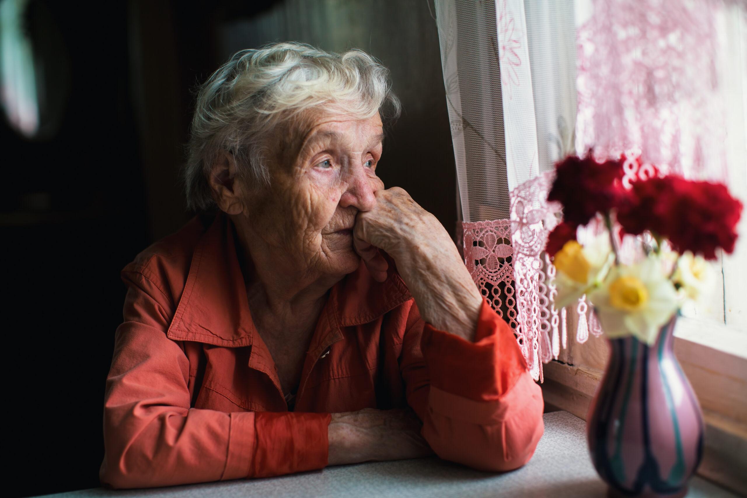 Eldre kvinne som sitter ved kjøkkenbordet og ser ut gjennom vinduet
